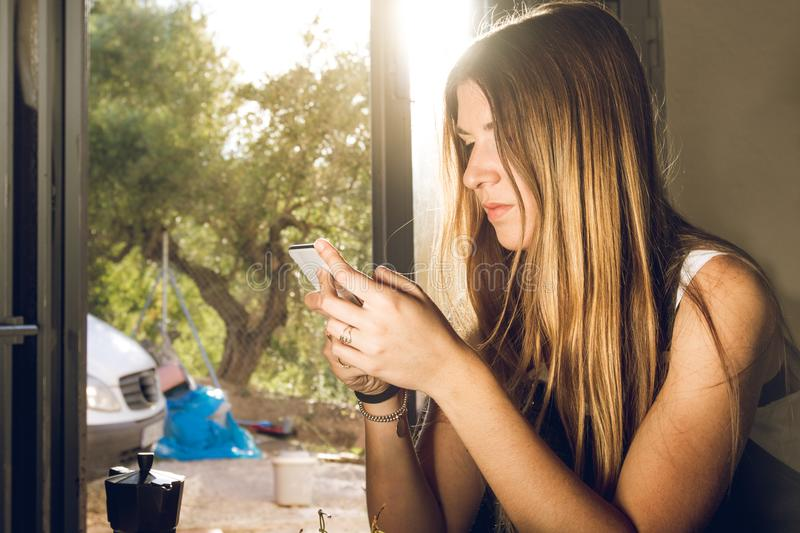 Young woman looking at her cell phone at home and drinking coffee royalty free stock photo