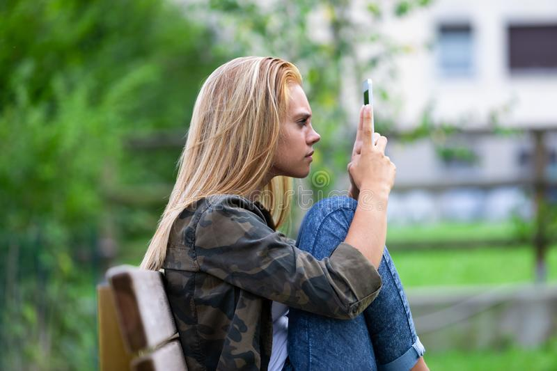 Young woman looking at her tablet on consternation. Lifting it close to her eyes as she relaxes in the garden on a bench royalty free stock photos