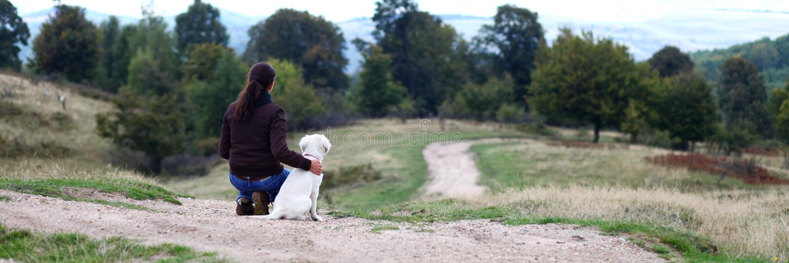Young woman looking in horizon with puppy stock image