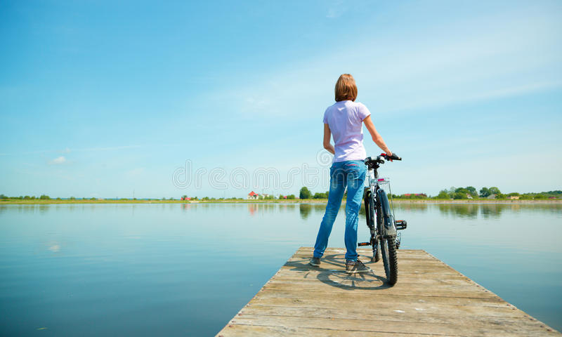 Young woman is looking at horizon. Standing on pier with bicycle, outdoor shoot royalty free stock images