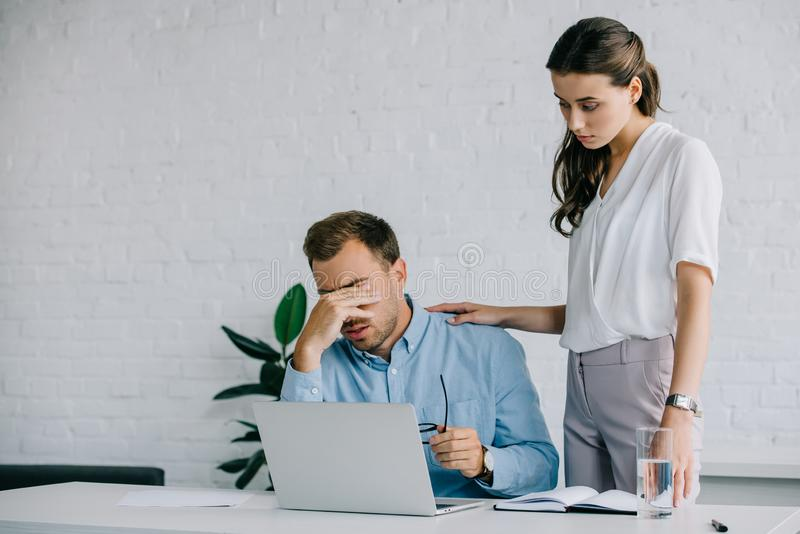 young woman looking at male colleague suffering from headache stock photos