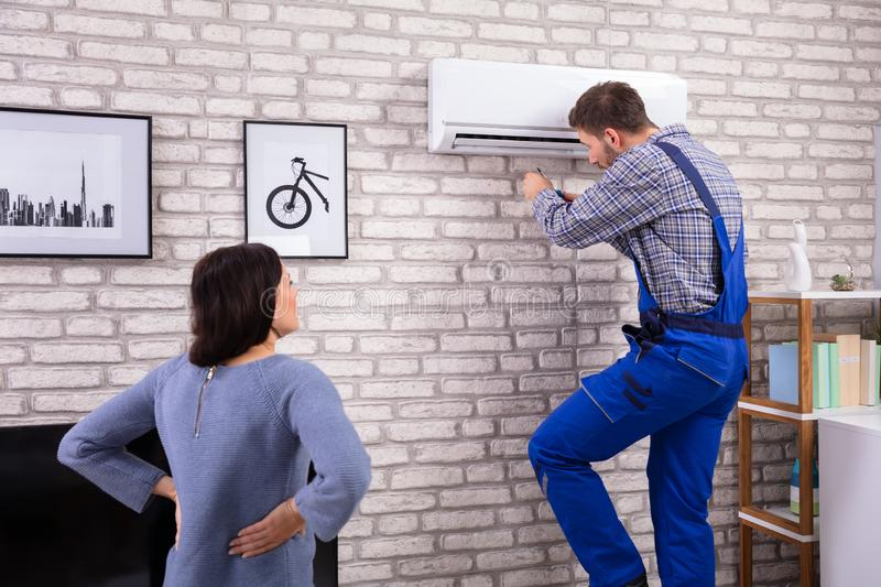 Woman Looking At Technician Repairing Air Conditioner stock photo