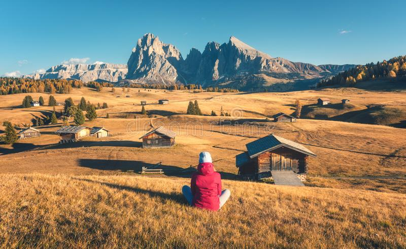 Young woman looking in meadows and mountains at sunset in autumn. Sitting woman on the hill looking on meadows and mountains at sunset in autumn. Alpe di Siusi stock image