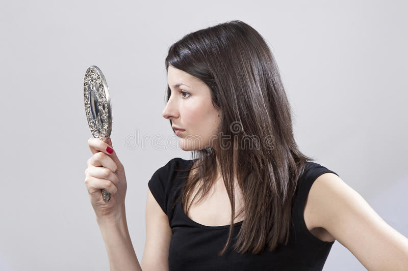 Young Woman Looking In A Mirror Stock Images