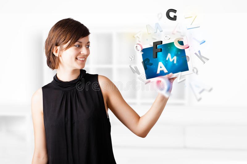 Young woman looking at modern tablet with alphabet. Young business woman looking at modern tablet with alphabet royalty free stock photography