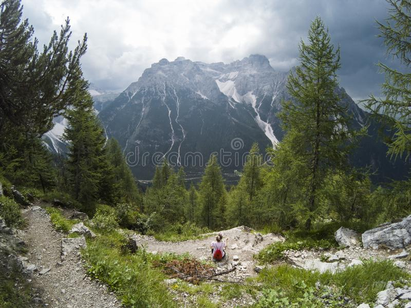 Young woman looking on mountains in front of her. Alps, Italy, Dolomites. Young girl traveler sitting with a view of the stock image