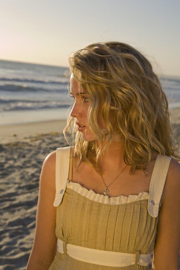 Young Woman looking at the Ocean. Beautiful Young Woman looking at the Ocean at Sunset royalty free stock photos