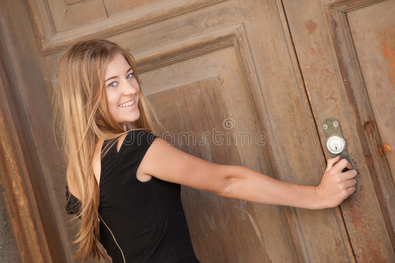 Young woman looking at an old door royalty free stock image