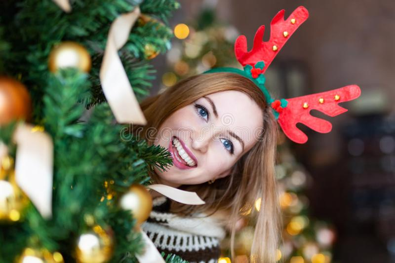 Young woman looking out of a Christmas tree wearing Christmas antlers of a deer. Happy woman looking out of a Christmas tree wearing funny Christmas antlers of a stock photography