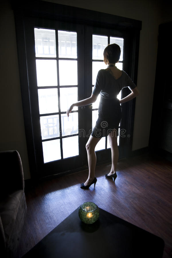 Young woman looking out window in dark room stock photo