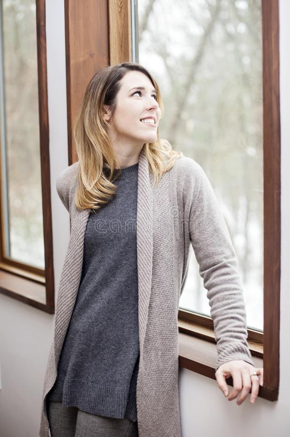 Young woman looking out window in winter. A smiling young woman looking out window at sky at home in winter stock image