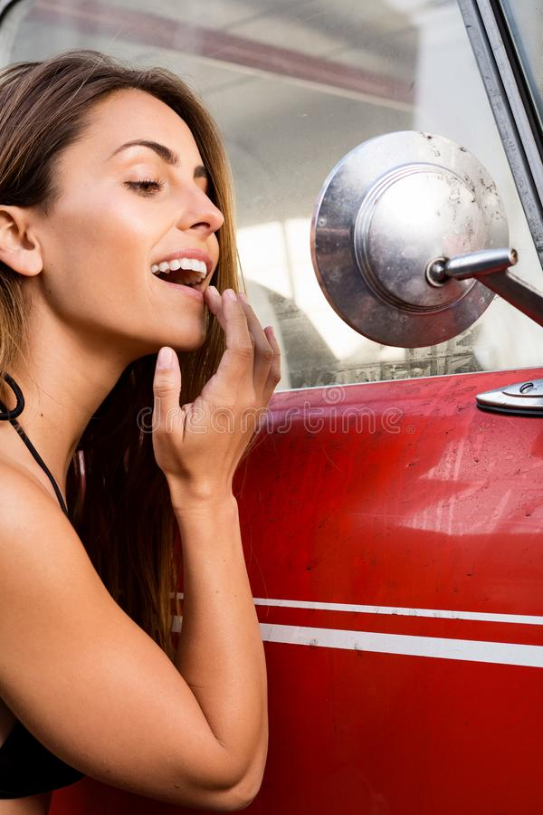 Young woman looking in outside mirror from vintage car. california lifestyle royalty free stock images
