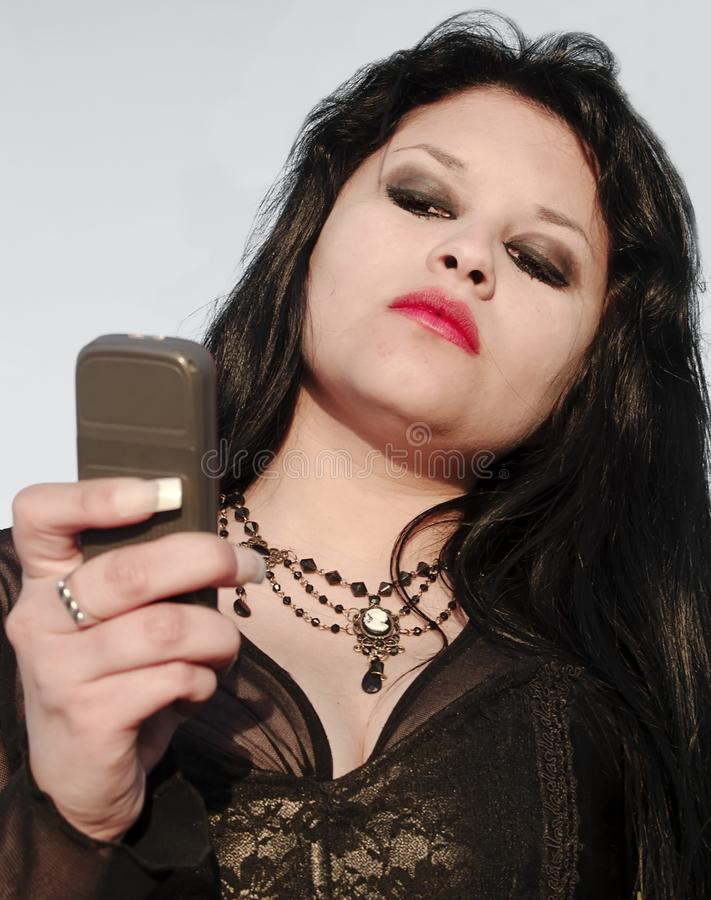 Young woman looking a phone. Gothic young woman posing outdoors at the seacoast of Valparaiso royalty free stock photography