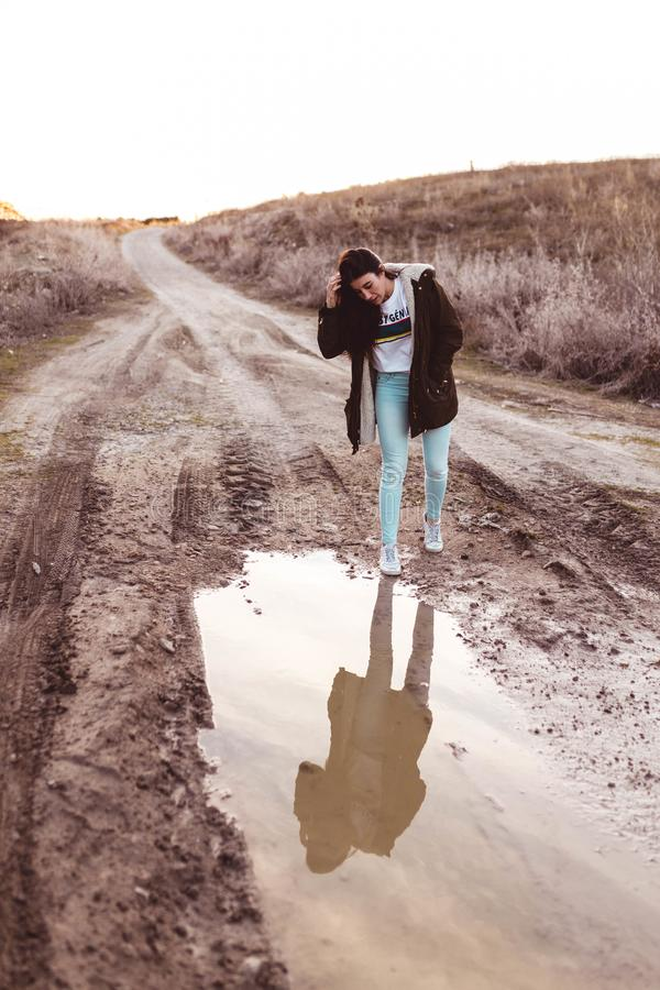 Young woman looking in the puddle at sunset in the countryside. One day stock images