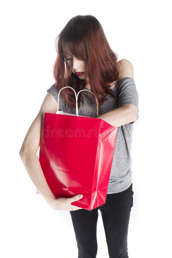 Young Woman Looking into Red Shopping Bag royalty free stock photography