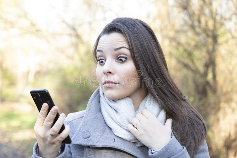 A young woman looking at the screen of her smartphone in the park stock images
