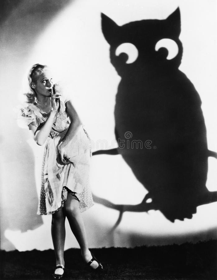 Young woman looking at a shadow of an owl with her finger on her lips stock photo