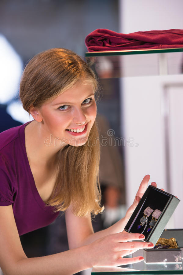 Young woman looking at the shop showcase and taking earrings royalty free stock images