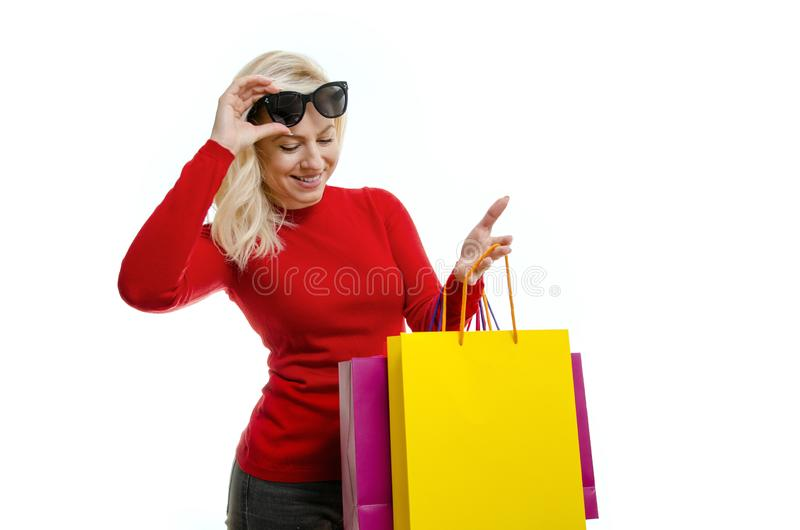 Young woman looking into shopping bags and smiling royalty free stock images