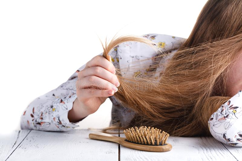 Young woman looking at split ends. Damaged long hair stock image