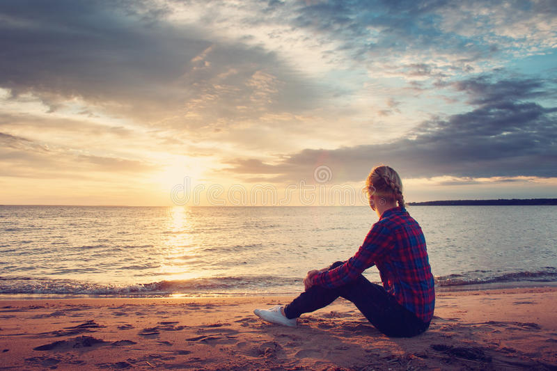 Young woman looking at sunset stock photography