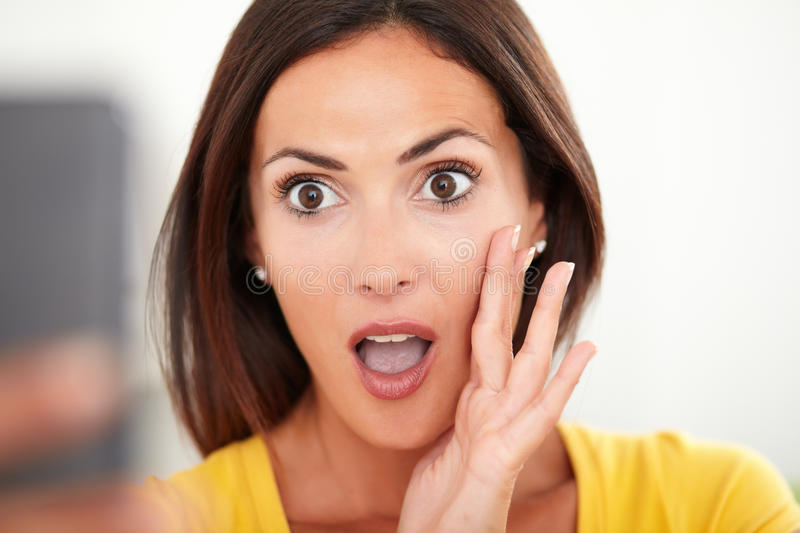 Young woman looking surprised while using a mobile stock photography