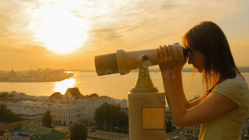 Young woman looking through tourist telescope, exploring historical part of city royalty free stock image