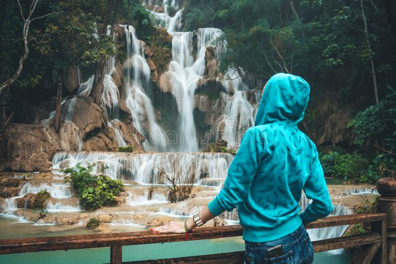 A young woman looks and admires the beautiful waterfall in the wild jungles of Asia.. Blonde Backpacker Or Traveler Girl in a Blue royalty free stock photo