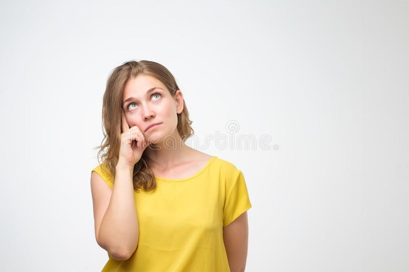 Young woman looks with doubt wears yellow t shirt, trying to make right decision. Pretty thoughtful caucasian young woman looks with doubt wears yellow t shirt royalty free stock image
