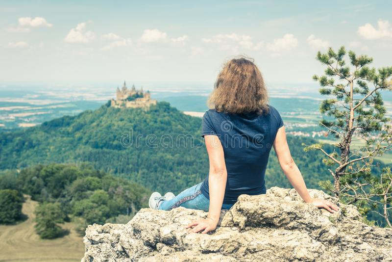 Young woman looks at Hohenzollern Castle, Germany royalty free stock photography