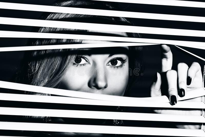 Young woman looks through the jalousie royalty free stock photo
