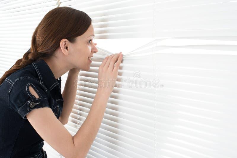 Young woman looks through jalousie stock photos