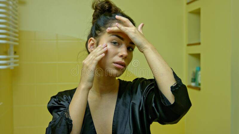 A young woman looks in the mirror and checks her first wrinkles royalty free stock photography