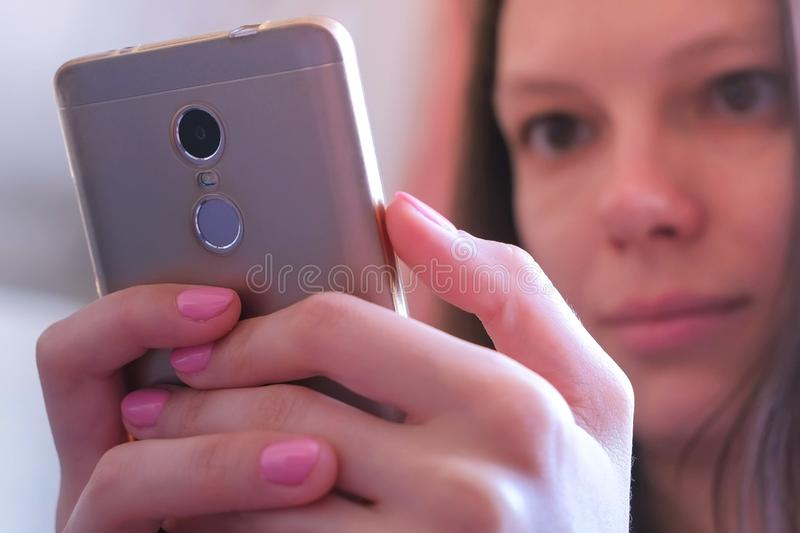 Young woman looks through and reads messages in smartphone holds in hands. Portrait of young woman looking at mobile phone screen with interest. She looks royalty free stock image