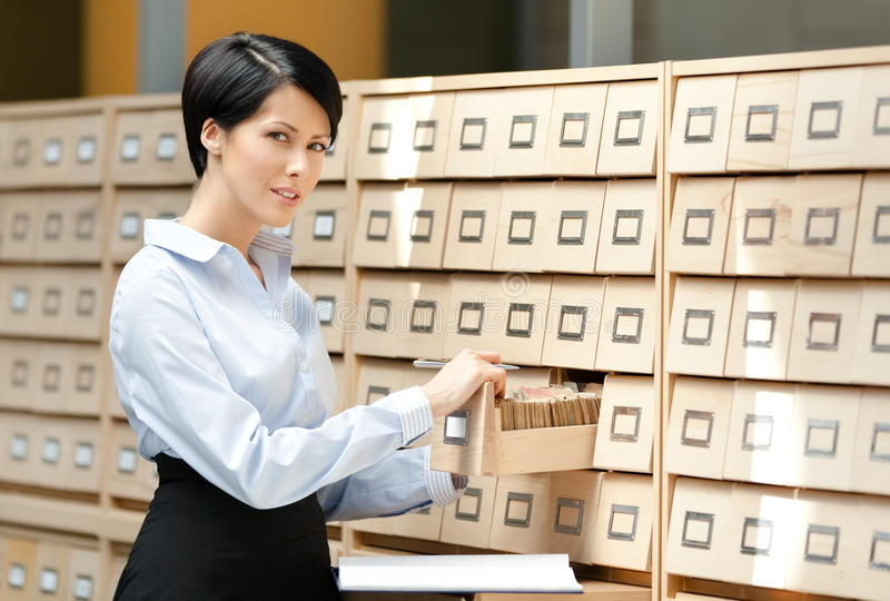 Download Young Woman Looks For Something In Card Catalog Stock Photo - Image: 27110464