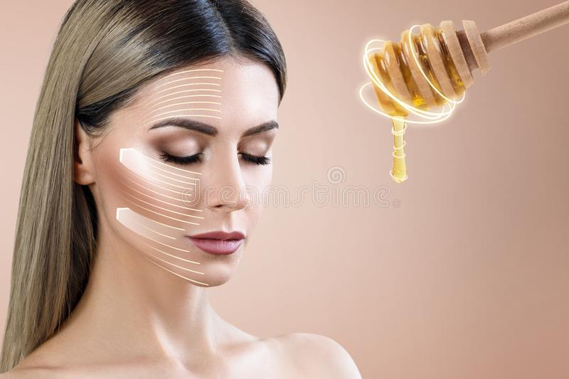 Young woman looks on spoon with honey and prepare for facial mask. Honey treatment concept royalty free stock images