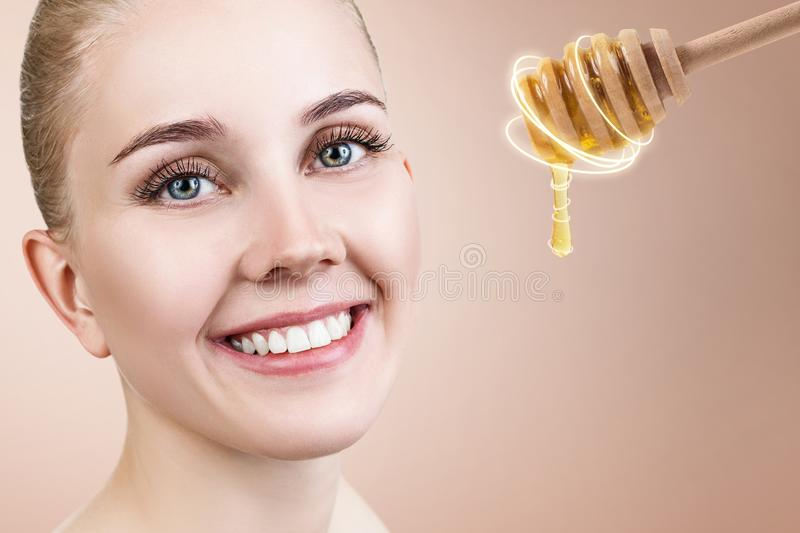 Young woman looks on spoon with honey and prepare for facial mask. royalty free stock image