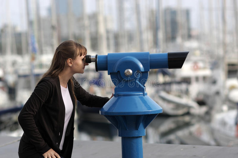 Young woman looks through telescope royalty free stock photos