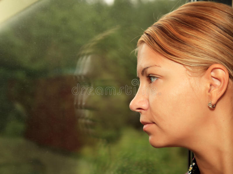 Young woman looks in train`s window stock photos