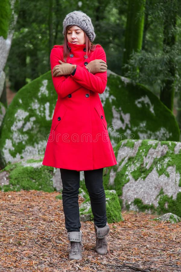 Young woman lost on a forest shivering with cold and embracing or holding herself royalty free stock photography