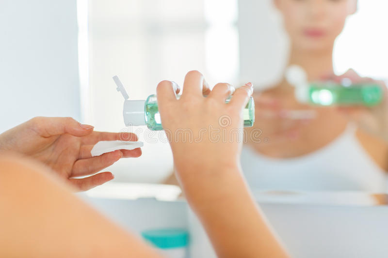 Young woman with lotion washing face at bathroom. Beauty, skin care and people concept - close up of young woman applying lotion to cotton disc for washing her royalty free stock photos