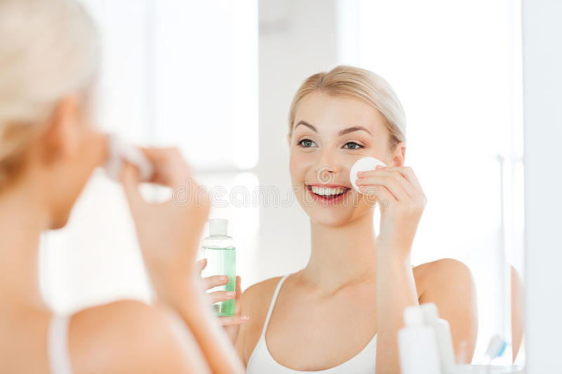 Young woman with lotion washing face at bathroom. Beauty, skin care and people concept - smiling young woman applying lotion to cotton disc for washing her face stock photo