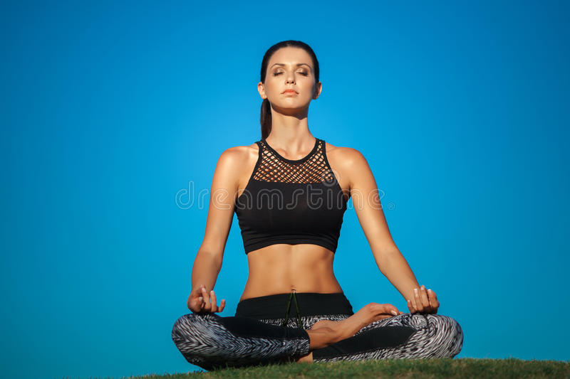 Young woman in lotus position. Attractive young woman in a lotus position in green park royalty free stock photography