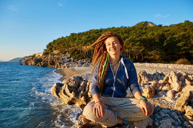 Young woman in the lotus position. Young woman with dreadlocks sitting in the lotus position on the cliff against sea and blue sky at early morning royalty free stock image