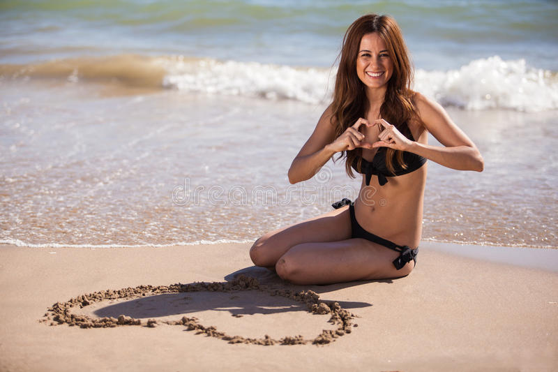 Young woman in love at the beach. Happy brunette doing a heart shape with her hands after drawing a heart in the sand royalty free stock photos