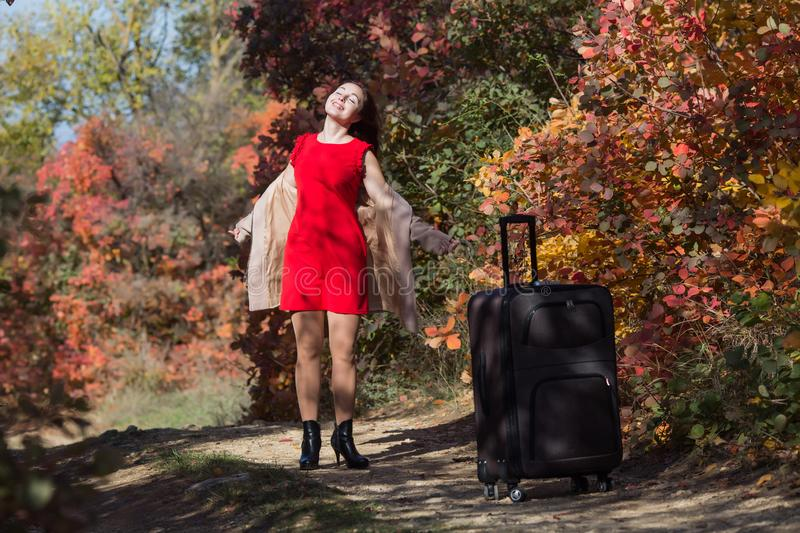 Young woman with the luggage on country road in the forest. Female person in short red dress and coat spinning arms outstretched royalty free stock images