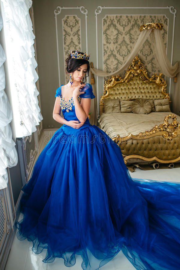 Young woman in a luxurious blue dress and a crown stock image