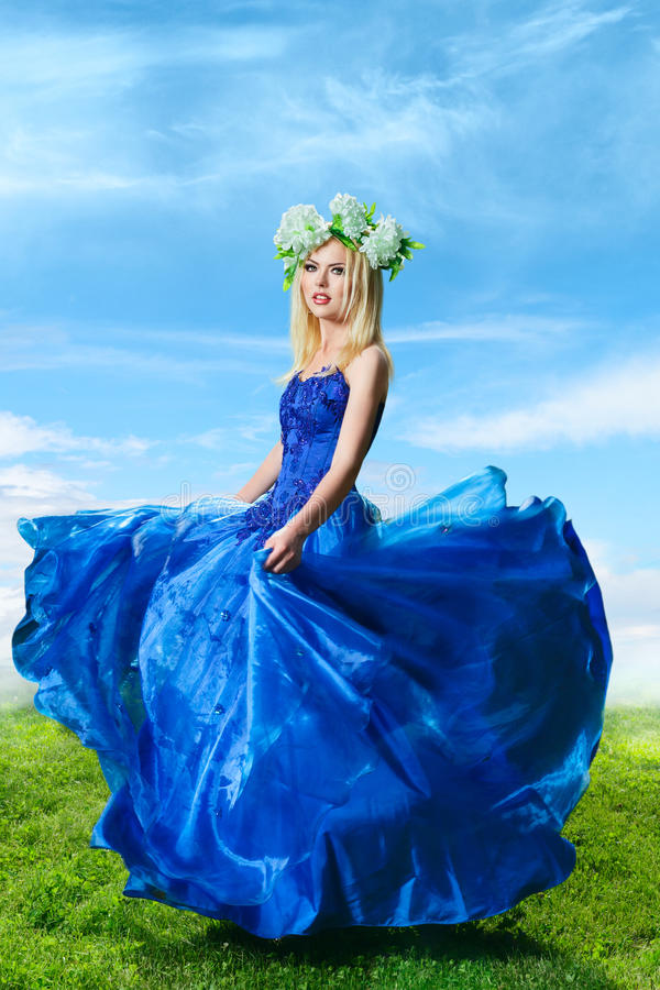 Young woman in luxurious blue dress. Young woman at outdoor fashion photoshoot demonstrating luxurious blue dress stock photography