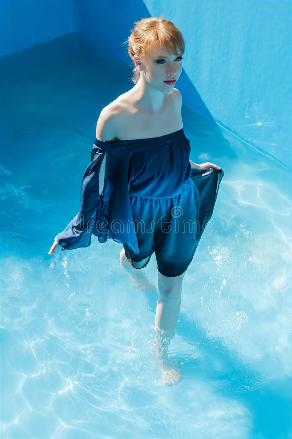 Young woman in luxurious blue dress. Young woman at outdoor fashion photoshoot demonstrating luxurious blue dress inside swimming pool stock photo