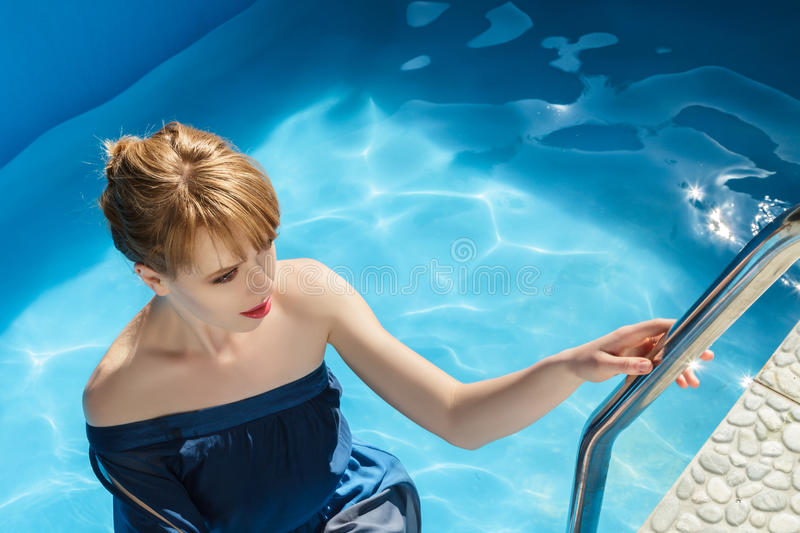 Young woman in luxurious blue dress. Young woman at outdoor fashion photoshoot demonstrating luxurious blue dress inside swimming pool stock image
